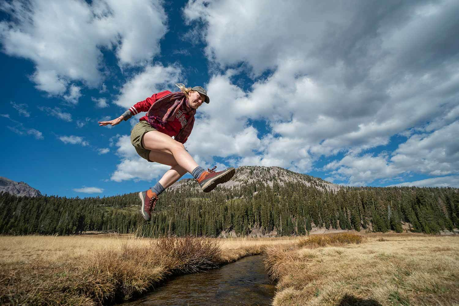 A student in a Chico State sweat shirt leaps heroically over a creek.