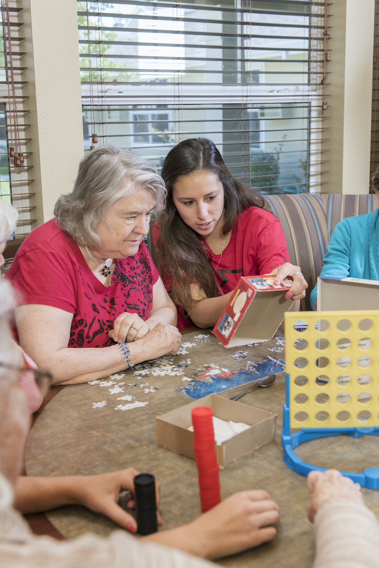 Photo of student with elderly woman playing games