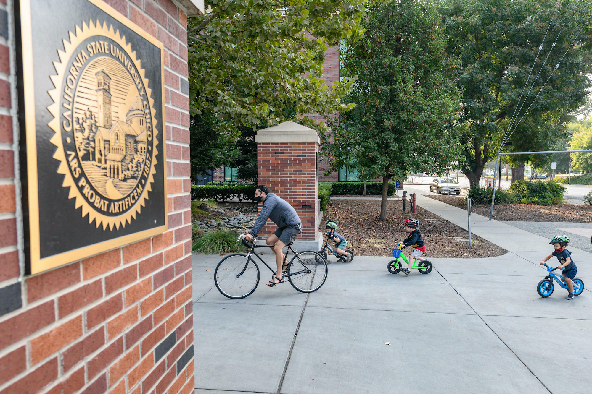 photo of adult and two children riding bikes